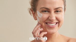 Sienna X brand image for skincare range. Blonde haired lady portrait photo. Shows the Lady smiling with skincare product on her left cheek