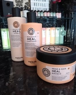 heal your hair and scalp. The image show the 3 products contained in the bundle. Peach in colour with black lids