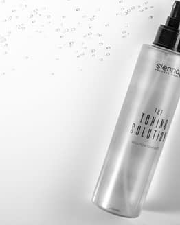 the toning solution by sienna x. The image shows a clear bottle with toning product inside, with a black pump spray applicator top. The product is laid down. All sienna x packaging is recyclable.