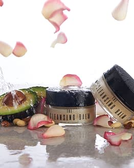 The Cleansing Balm by Sienna X. The image shows two jars of the product with rose petals and an avocado cut in half. These are some of the ingredients in the product.