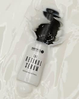the retinol serum by sienna x. The image shows the product bottle slightly submerged in liquid.